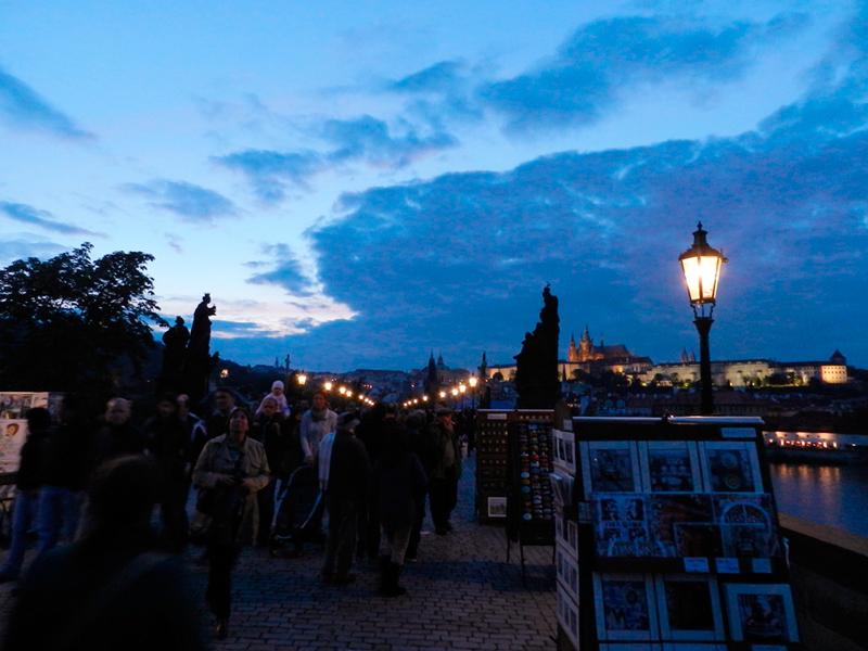 Karlův most à noite com ambulantes em Praga
